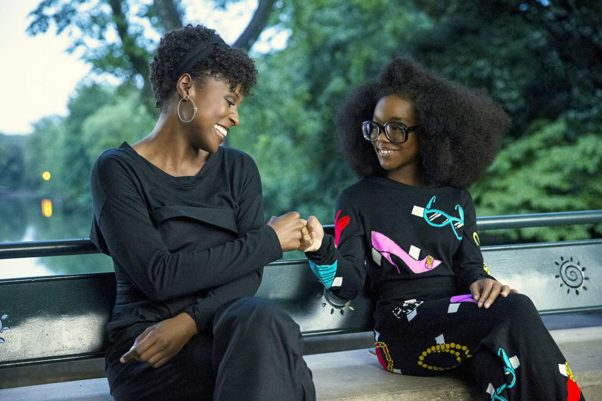 Issa Rae (April) and Marsai Martin (Jordan) fist bump while sitting on a park bench. (Photo: Universal Pictures)