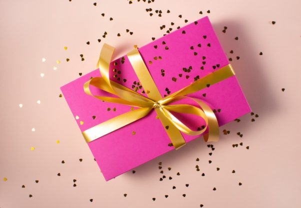 Present wrapped in pink paper with a gold bow and covered with confetti.