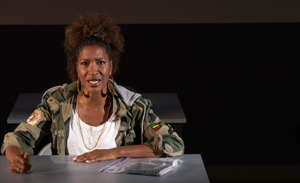 Actress Liza Jessie Peterson sitting at a table in a prison visiting room. (Photo: WoollyMammoth Theatre Co.)