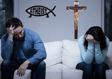 A sad couple sitting on a couch with an athesist symbol behind him and a cross behind her. (Photo: Shutterstock and Patheos)