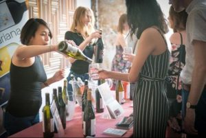 A woman pouring a wine sample into a glass held by another woman. (Photo: D.C. Wine Fest)
