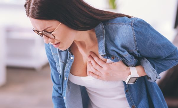 Woman clutching her chest. (Photo: Dr. Axe)