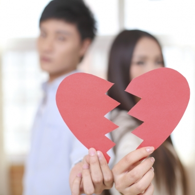 AnAsian couple out of focus in the background holidng a broken paper heart in the foreground. (Photo: iStock)