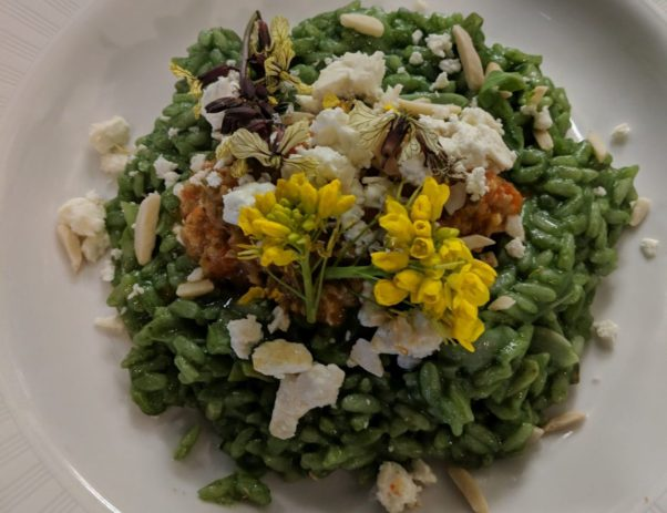 Dish & Dram's nettle risotto in a white bowl topped with  toasted almond slivers and local edible baby yellow flowers. (Photo: The Dish & Dram)