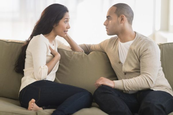 A Hispanic couple having a confersation sitting on a couch. (Photo: Getty Images)