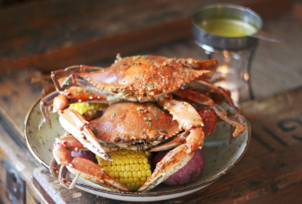 3 crabs on top of potatoes and corn on the cob on a plate. (Photo: Morgan West)