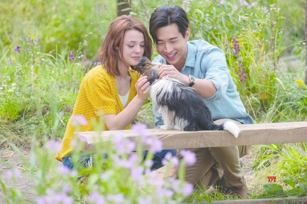 CJ (Kathryn Prescott, left) and Trent (Henry Lau, right) pet Max. (Photo: Universal Pictures)
