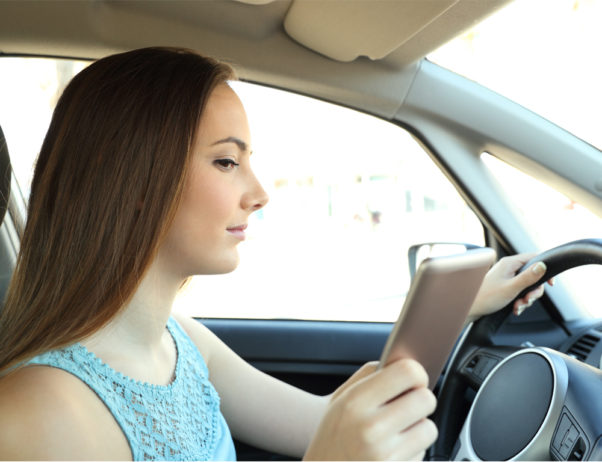 Teen female driver looking at her cell phone while driving. (Photo: Getty Images)
