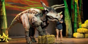 An emcee with a life-size dinosaur puppet. (Photo: Smithsonian National Zoo)
