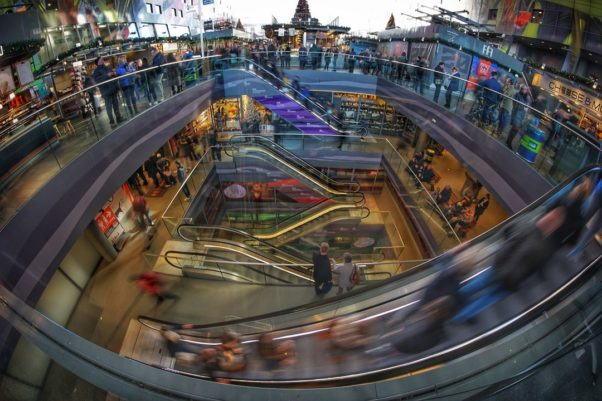 Shoppers in a mall going up and down escalators. (Photo: Dieter de Vroomen/Pexels)