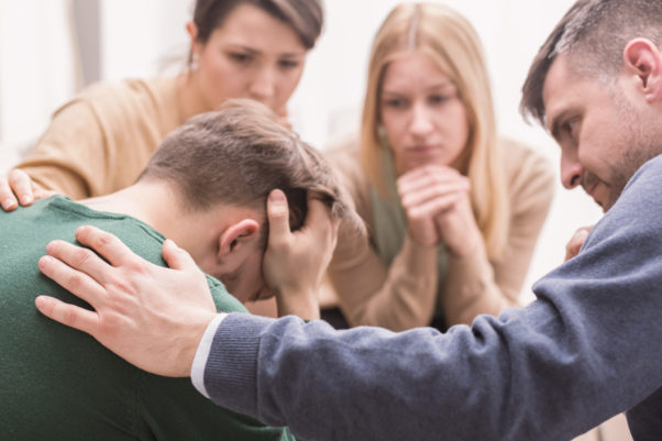 Close-up of a devastated young man holding his head in his hands and friends supporting him during group therapy. (Photo: iStock)