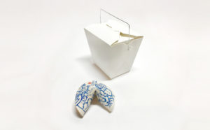 """A mass produced white and blue """"fortune cookie"""" andwhite Chinese food take-out box by Jiha Moon. (Photo: Jiha Moon)"""