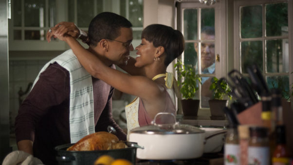 Michael Ealy and Meagan embrace in the kitchen while Dennis Quaid peers in through a window. (Photo: Sony Pictures)