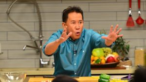 Martin Yan in a kitchen talking with his hands outstretched. (Photo: Rongsheng Liu)