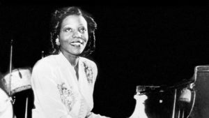 Black and white photo of Mary Lou Williams sitting at a table. (Photo: Kennedy Center)