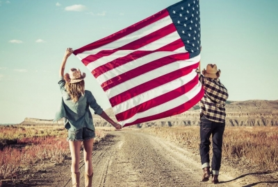 Young couple wearing cowboy hats carry a huge US flag down a dirt road towards some plateaus. (Photo: Getty Images)