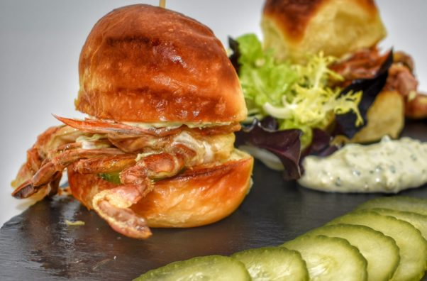 Two soft shell crab sliders with chili garlic pickles and house tartar sauce on buttered Parker House rolls on a piece of slate. (Photo: Mirabelle)