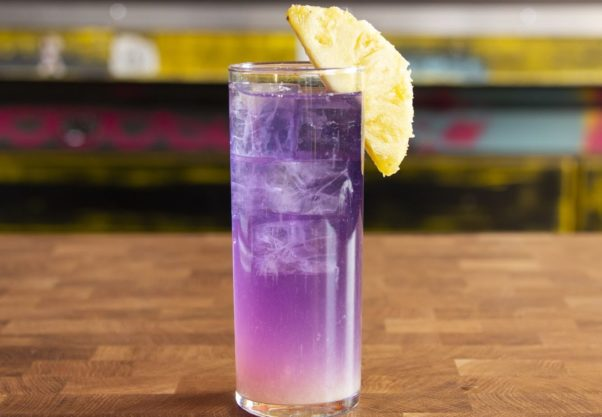 The Spring Awakening cocktail -- a purple cocktail in a tall glass with a slice of pineapple on the rim. (Photo: Casey Kaufman)