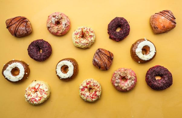 14 of Astro Doughnuts May flavors laying on a yellow counter. (Photo: Jennifer Chase)