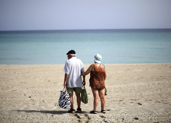 Old man and woman standing on a deserted beach in Cuba with their beach supplies. (Photo: David Gilkey/NPR)