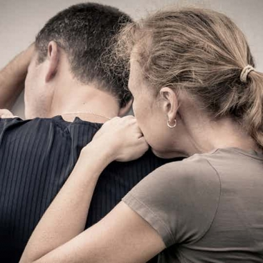 Woman holding sad man from behind with his head in his arms agains a wall. (Photo: Shutterstock)