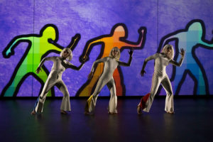 Three somen dressed in white dancing in front of their sillouettes in green, red and yellow on a blue background. (Photo: Kennedy Center)