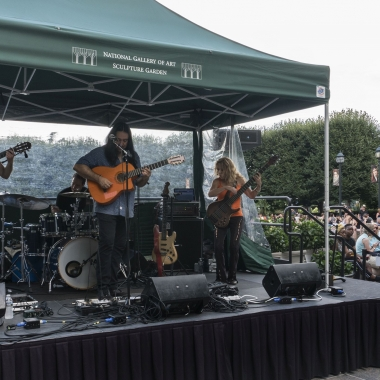 Three musicians perfomring under a canopy in front of the National Gallery of Art's fountain. (Photo: National Gallery of Art)
