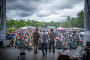 A band of 3 men perform at a past Kingman Bluegrass & Folk Festival with a crowd gathered around the stage. (Photo: Kingman Bluegrass & Jazz Festival)