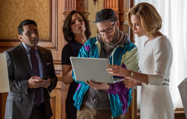 Seth Rogen and Charlize Theron look at a laptop. (Photo: Lionsgate Films)