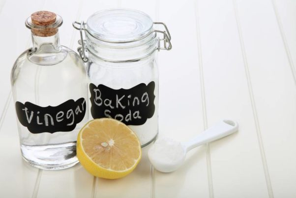 clear jars labeled viengar and baking soda sitting beside a half lemon and spoon. (Photo: Shutterstock)