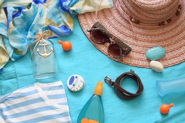 Sunscreen, sunglasses, a wide-brimmed hat, blue stripped shirt and other trinkets lying on an aqua blanket. (Photo: marijana1/Pixabay)
