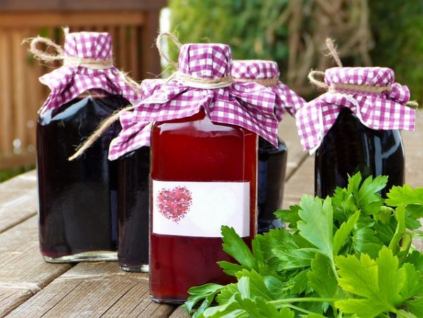4 bottles of homemade syrups with checkered cloth covering the lids. (Photo: Silviarita/Pixabay)