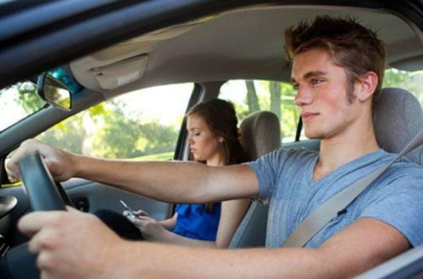 Teen girl passenger looking a phone while teen boy drives. (Photo: Shutterstock)