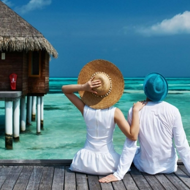 Couple dressed in white wearing hats sitting on a dock in front of a thatch hut looking out at clear blue water & a blue sky. (Photo: Getty Images)
