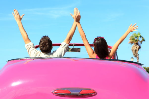 Happy couple in pink vintage retro car with arms raised. (Photo: Shutterstock)