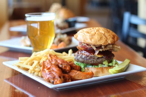 A plate with a buger, wings and fries on it sitting beside a glass of beer. (Photo: Velocity Wings)