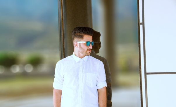 A man leaning against a glass wall with a white Oxford shirt with the arms rolled up and sunglasses. (Photo: Awar Jahfar/Unsplash)