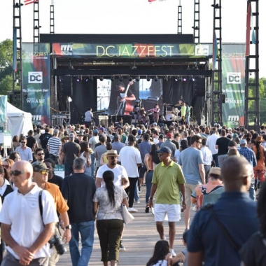 People at the D.C. Jazz Festival walking on a pier at The Wharf in front of the stage. (Photo: D.C. Jazz Festival)