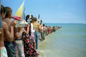 """Photo """"Don't Cross the Bridge Before You Get to the River"""" of people standing in the ocean holding toy boats. (Photo: Francis Alys)"""