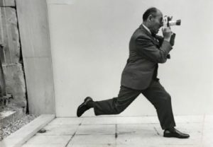 Black and white photo of Albert Eisenstaedt running in a suit while hold the camera up to his eye. (Phhoto: Phillippe Halsman)