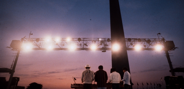Four singers on a stage on the National Mall with their backs to the camera and the Washington Monument in the background. (Photo: Smithsonian Folklife Festival)