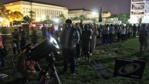 Visitors wait in line to look through teescioes at the Astronomy Festival on the National Mall. (Photo: Geoff Chester)
