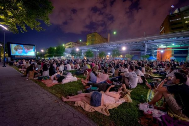 People sitting on blankets in Georgetown's Waterfront Park watching an outdoor movie. (Photo: Sam Kittner)
