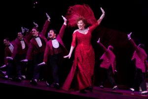 Betty Buckly in Hello, Dolly! dresed in red dress and hat dancing with several men in tuxes. (Photo: Julieta Cervantes)