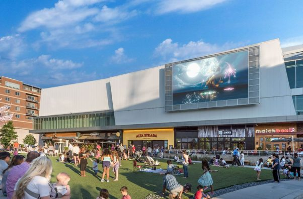 People sitting in Mosaic District's Strawberry Park on the big screen above Matchbox, Jinya and Alta Strada restaurants. (Photo: Mosaic District)