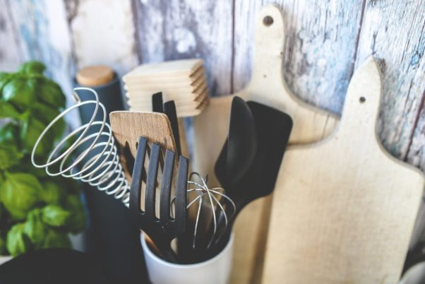 A cup holding assorted kitchen tools in front of two cutting boards. (Photo: Kaboompics/Pexels)