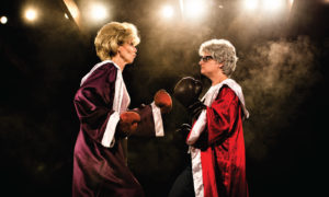 Two older wome dressed in boxing gowns and robes staring each other down. (Photo: Keegan Theatre)