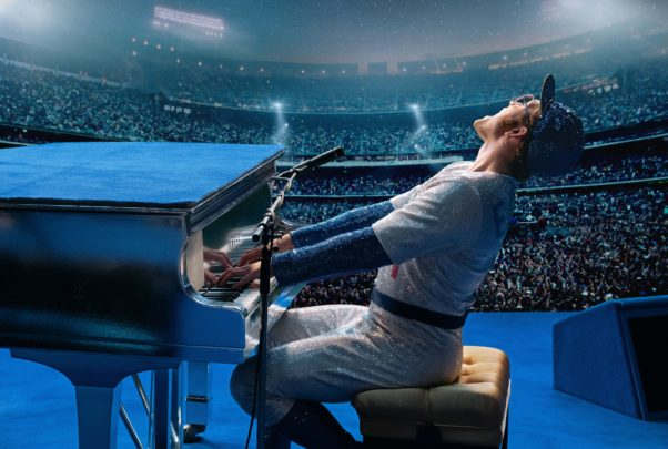 Taron Egerton as Elton John plays the piano on stage dressed in a sequined baseball uniform. (Photo: Paramount Pictures)