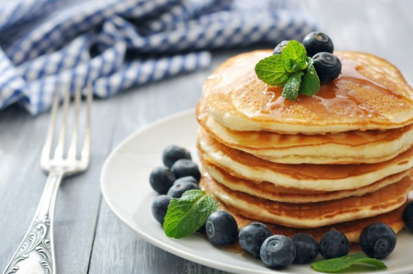 Pancakes with fresh berries, mint and maple syrup on white plate closeup. (Photo: Shutterstock)