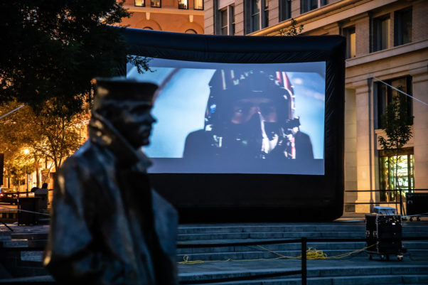 A scene from Top Gun is shown on a screen with the Lone Sailor Statue in the foreground. (Photo: U.S. Navy Memorial)